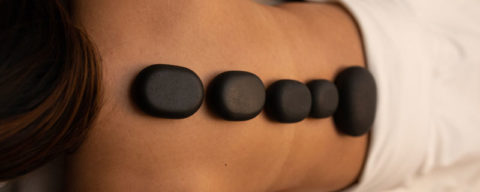 A photo of a client receiving a hot stone massage at Evolve Salon & Spa