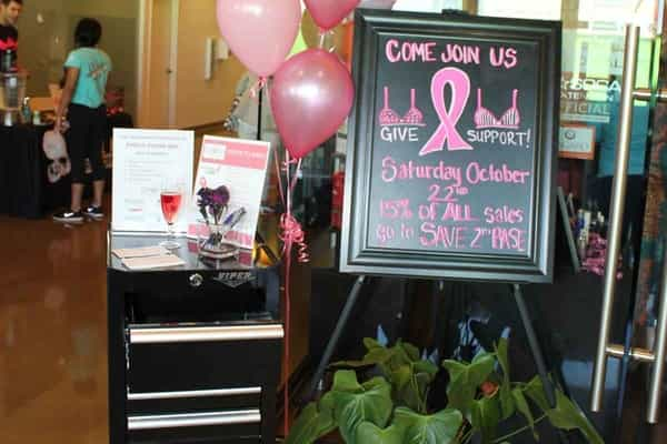 Display signs in front of Evolve Salon & Spa for breast cancer awareness charity event welcome table