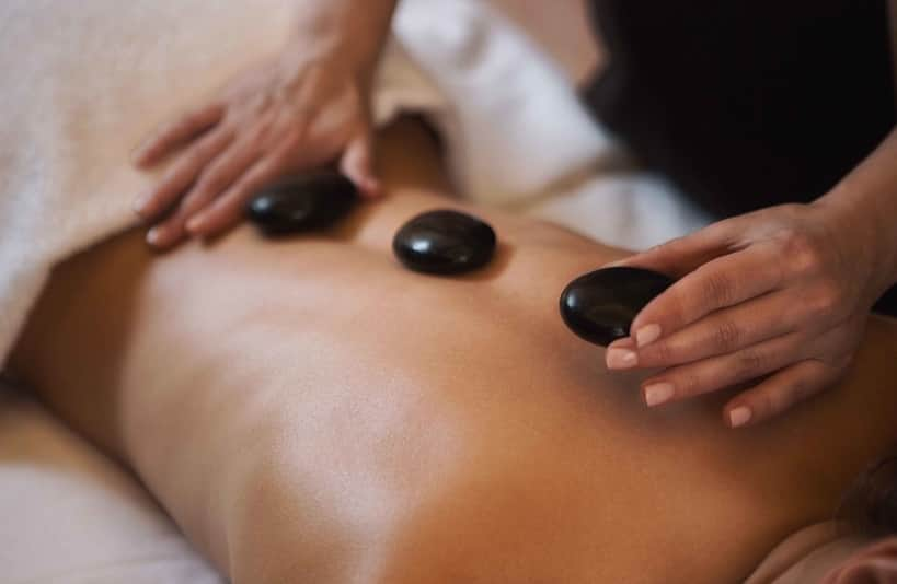 An Evolve Salon and Spa client receives a hot stone massage add-on to an Evolve Signature Swedish Massage