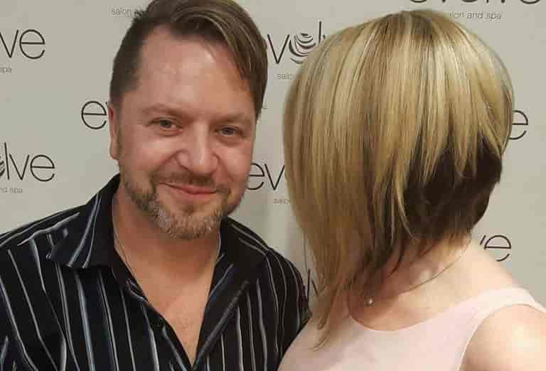 Evolve Salon and Spa Owner Chris Whitmore stands with an Evolve Stylist